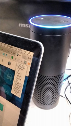 A photo of an Amazon Echo, behind a laptop displaying the Chromelexa plugin